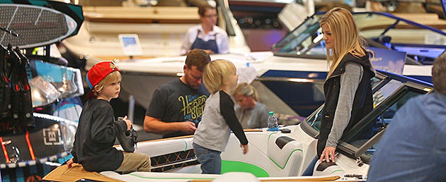 Family explores the bow of a new Nautique