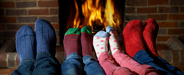 Family's feet in socks by the fireplace